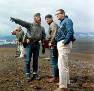 Astronaut Dave Scott pointing out a geologic feature to astronaut Gene Cernan and Elbert A. King on the rim of the Askja Caldera